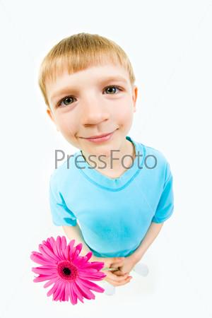 Милый мальчик стоит с улыбкой, держа в руках розовый цветок