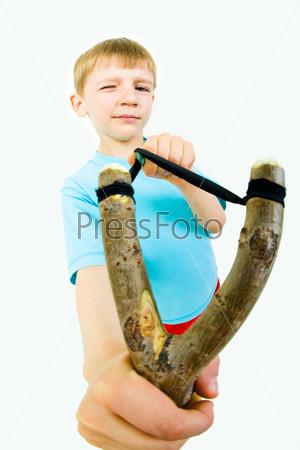 Крупный план рогатки, которую, прищурившись, натягивает мальчик
