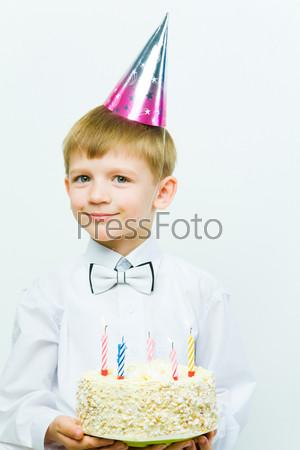 Фотография на тему Мальчик в праздничном колпаке стоит с большим тортом со свечами