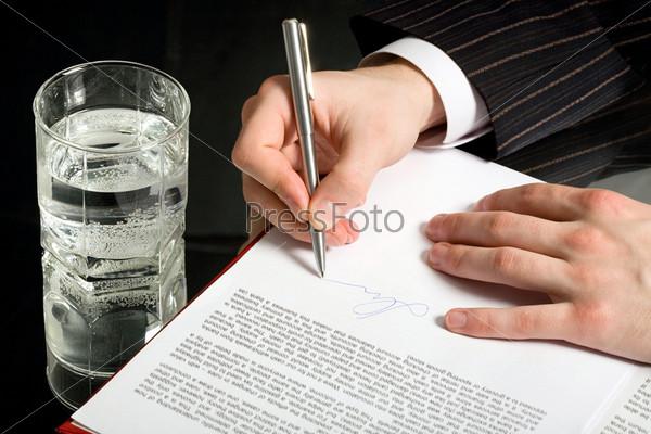 Крупный план руки бизнесмена подписывающего документ