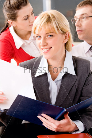 Деловая женщина с раскрытой папкой улыбается глядя в камеру на фоне своих коллег