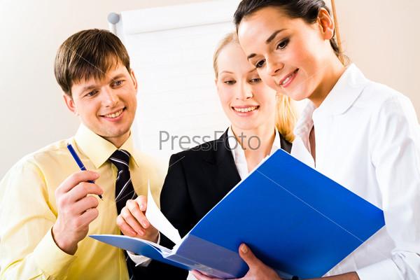 Сотрудники заглядывают в папку с документами, которую держит секретарь