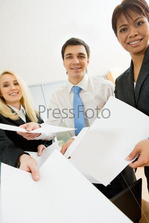 Приветливые менеджеры улыбаясь предлагают бланки для заполнения