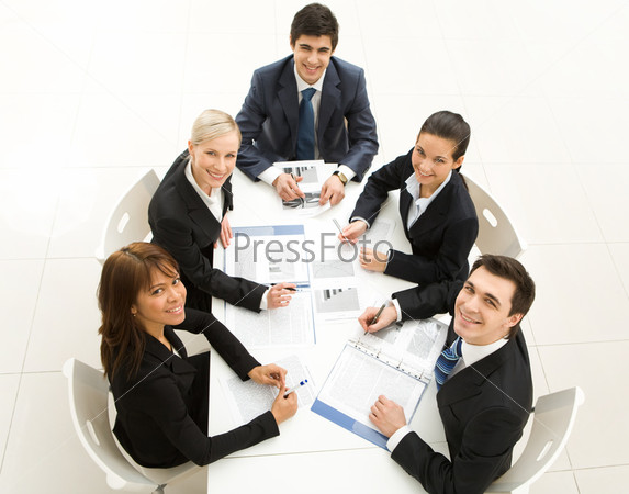 Офисные работники сидят вокруг стола и улыбаясь смотрят наверх в камеру