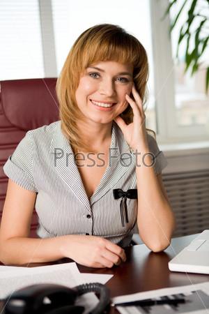 Сотрудница улыбается на рабочем месте