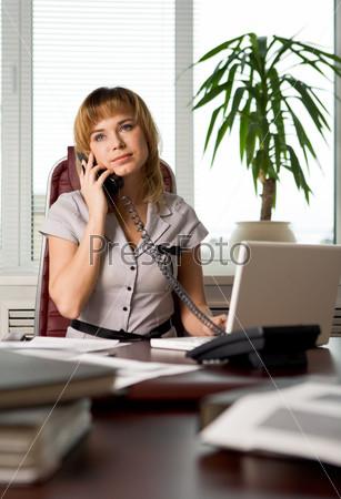 Сотрудница разговаривает по телефону в офисе с серьезным выражением лица