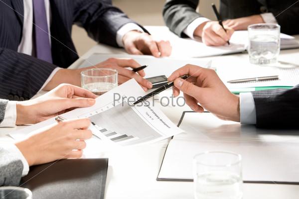 Руки бизнесменов, работающих с документами во время командной работы