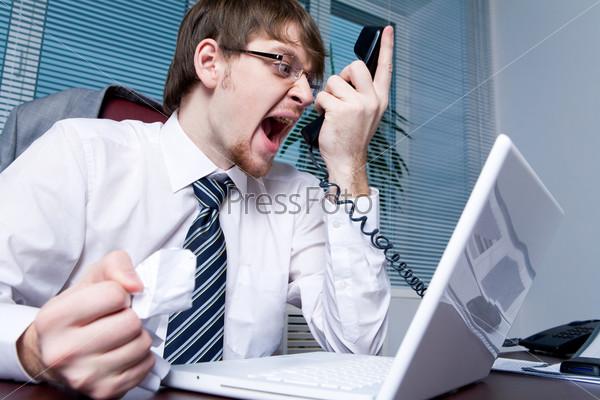 Раздраженный начальник кричит в телефонную трубку