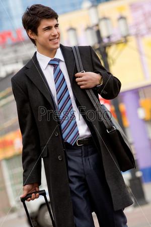 Успешный предприниматель идет по центральной улице города и смотрит по сторонам