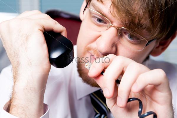 Разгневанный бизнесмен пытается воткнуть телефонный штекер в трубку