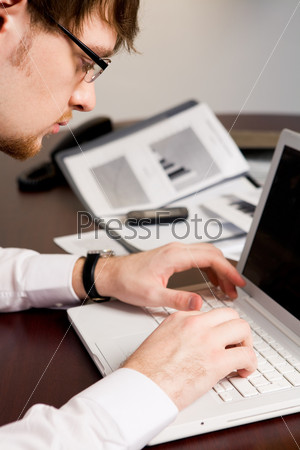 Серьезный молодой человек печатает в ноутбуке новые идеи по поводу бизнес проекта