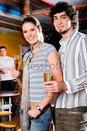 Молодая пара стоит в ночном клубе и улыбается глядя в камеру