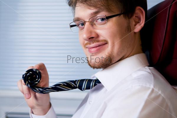 Солидный генеральный директор улыбается и сматывает галстук