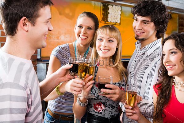 Компания друзей в кафе с бокалами в руках