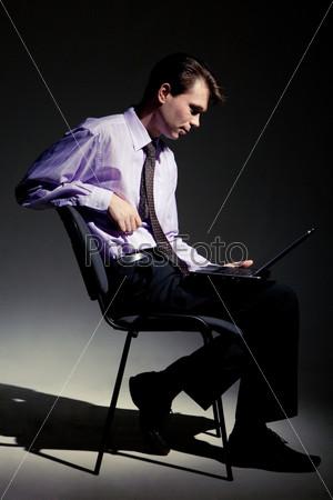 Бизнесмен сидит на стуле в темной комнате и смотрит на экран ноутбука