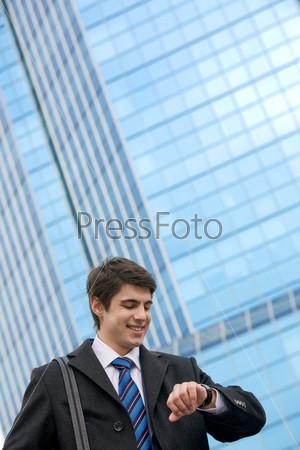 Солидный бизнесмен смотрит на часы и улыбается