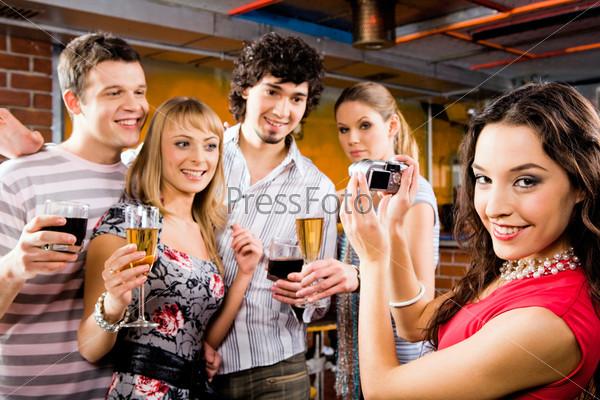 Веселая компания друзей фотографируется в кафе