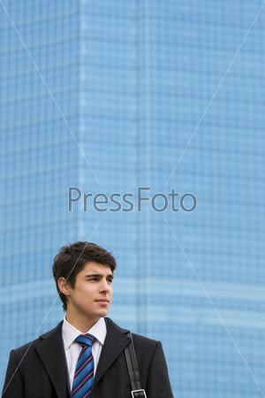 Задумчивый молодой человек смотрит в сторону на фоне современного офисного здания