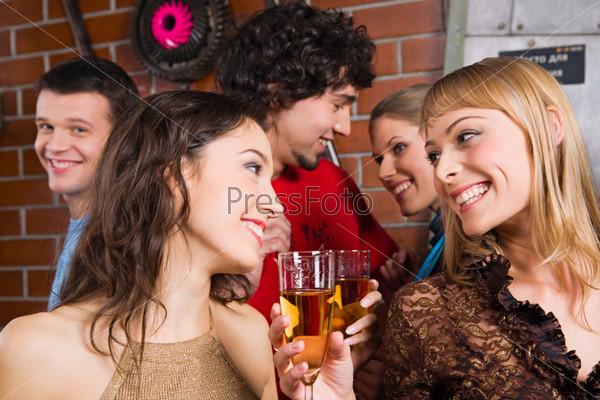 Фотография на тему Две веселые девушки общаются в баре с бокалами шампанского