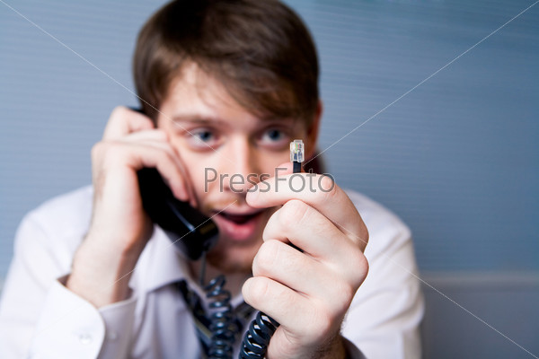 Молодой человек держит в руке телефонный штекер