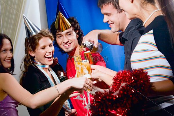 Шумная компания студентов в забавных колпаках веселится на вечеринке