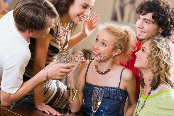 Веселые молодые люди общаются на вечеринке в кафе