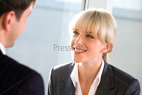 Деловая блондинка внимательно слушает своего собеседника и улыбается