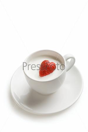 Клубника в форме сердца в чашке с молоком на белом фоне