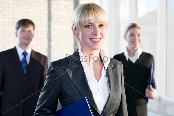 Молодая деловая женщина стоит на фоне своих коллег