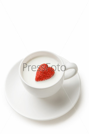 Красная клубника в форме сердца в чашке с молоком