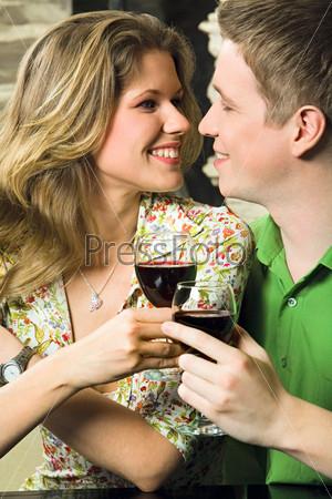 Фотография на тему Парень с девушкой смотрят друг на друга держа в руках бокалы с вином
