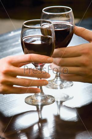 Два бокала с красным вином стоят на столе