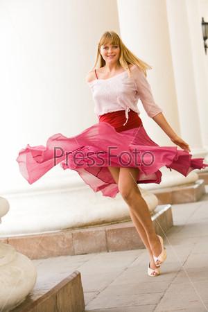 Красивая девушка кружится в розовой юбке на фоне колонн