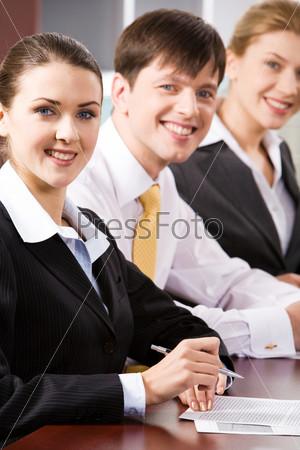 Довольные бизнесмены с улыбками сидят в ряд за столом