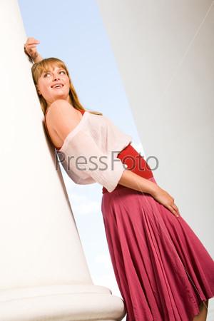 Стильная девушка в розовой юбке стоит на улице у стены и улыбается