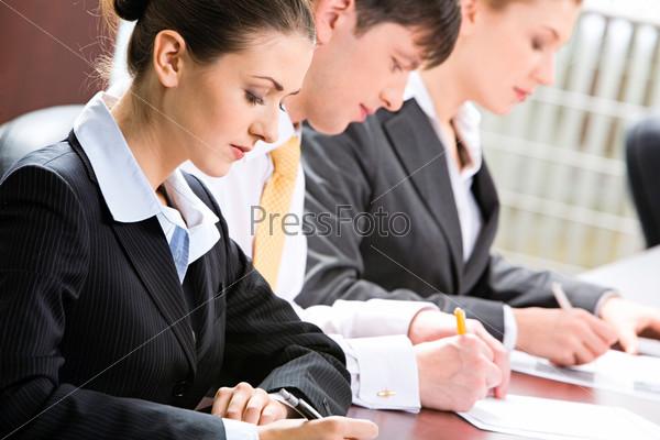 Трое сотрудников усердно делают записи сидя в ряд за столом