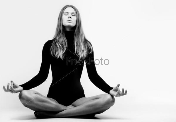 Красивая девушка медитирует сидя на полу