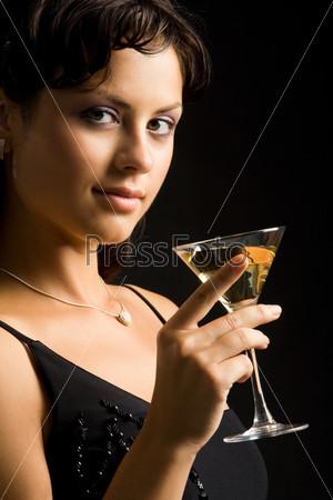 Изящная девушка в черном платье с бокалом коктейля в руках