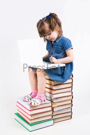 Школьница сидит на книгах и учиться пользоваться ноутбуком