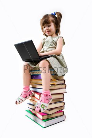 Первоклассница сидит на книгах и печатает на ноутбуке
