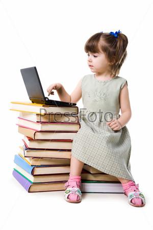 Маленькая девочка сидит перед ноутбуком на книгах
