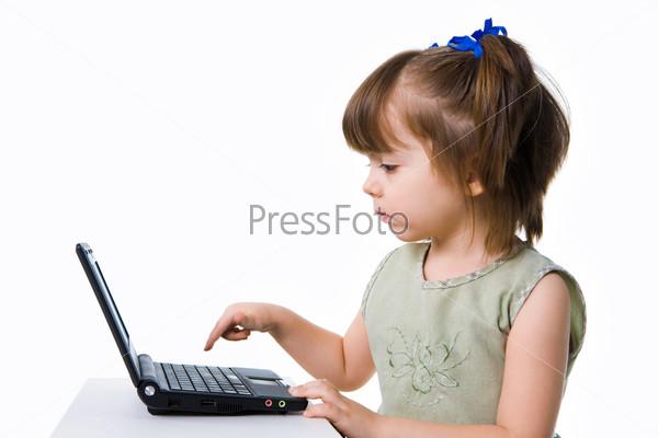 Девочка со всей серьезностью нажимает на клавиши ноутбука