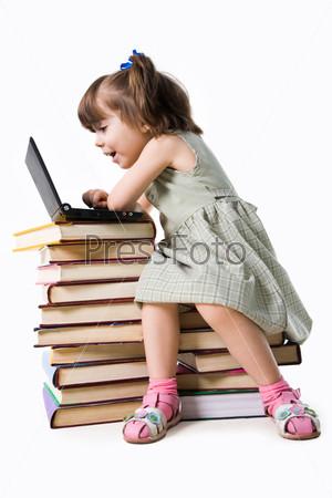 Удивленная девочка дошкольного возраста сидит на книгах перед ноутбуком и смотрит с открытым ртом на экран