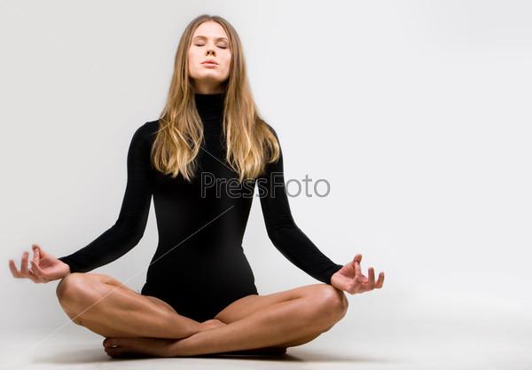 Сексуальная девушка медитирует в позе лотоса