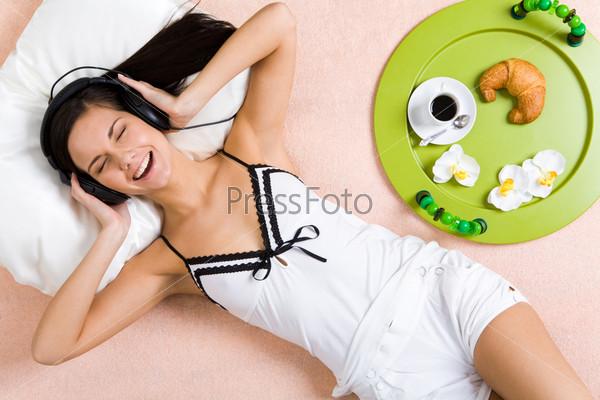 Привлекательная девушка с удовольствием слушает музыку в наушниках