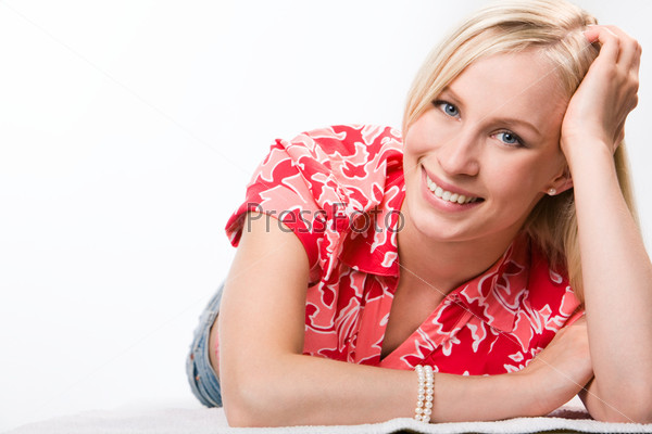 Девушка в красной рубашке лежит на полу и улыбается
