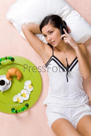 Девушка лежит на кровати и разговаривает по сотовому телефону