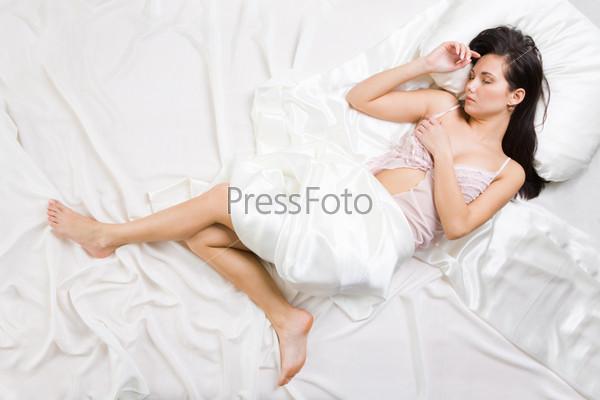 Привлекательная девушка в пеньюаре спит на шелковых простынях