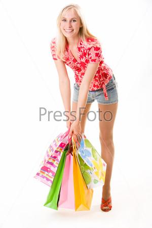 Красивая девушка поднимает пакеты с покупками