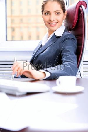 Успешная деловая женщина сидит в кресле за рабочим столом